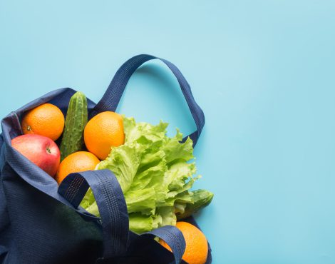 Zero waste concept. Blue shopping textile bag with fresh orange and vegetables. Space for text. View from above.